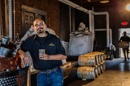 Man Sipping a Drink in a Distillery