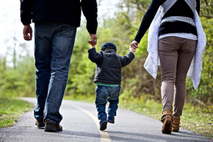 Parents Walking With Their Child Photographed From Behind