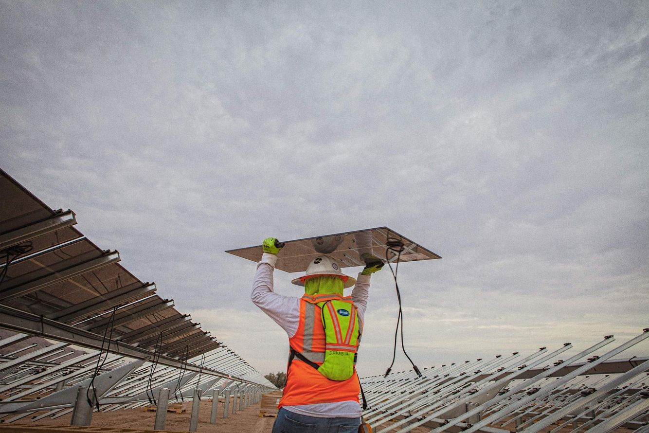 Worker Walking Holding a Solar Panel Over His Head