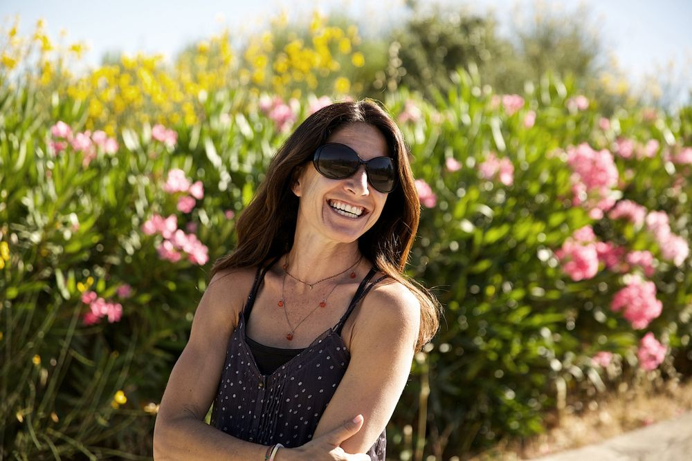Woman Laughing Outside In front of Wild Flowers