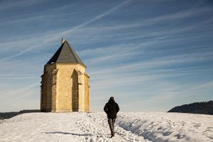 Man Walking In Snow To a Tiny Church