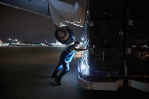 Worker Pushing Cargo Toward a 747 Cargo Transportation Plane