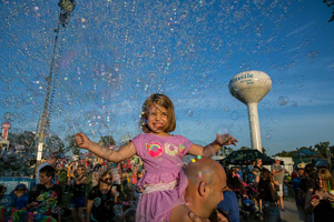 Girl On Shoulders Surrounded By Bubbles