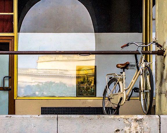 locked bike, distant crucifix, building reflectionion