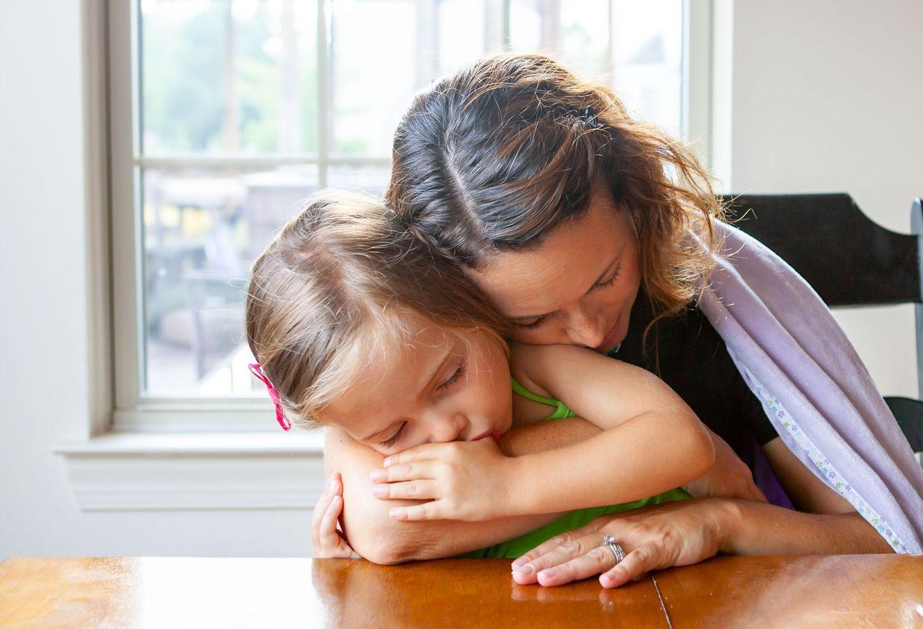 Mom cuddles girl