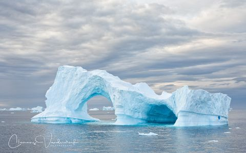 iceberg-with-hole-drifting-in-late-evening-light_s6a8749-lemaire-channel-antarctica.jpg