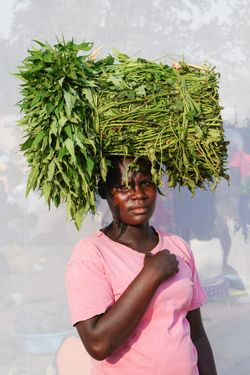Apiyo Kevin. Age 24. Selling sweet potato vines for 2,000 UGX per bundle for 7 years.