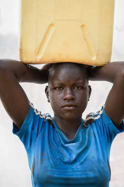 Akello Sarah (age 13) carries a 5-gallon jerrycan of water three times a day for home use .