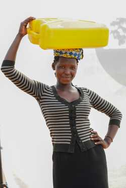Adong Daphine (age 20) carries 5-gallon jerrycan of water for home use twice a day.