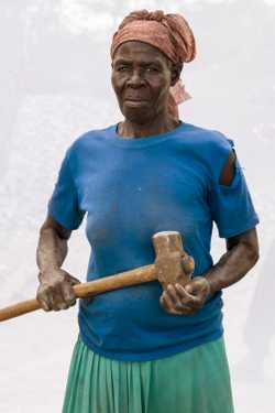 Akello  Olga (age 74) working in quarry for 28 years. Breaking stones to gravel size, filling about six  jerrycans of gravel per day at 1,000 shillings per ($0.32 USD).