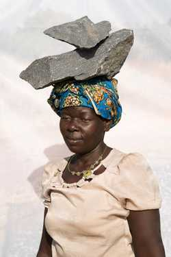Abur Janet (age 38) working In quarry for 10 years.  Breaking stones to gravel size, filling 10 jerrycans of gravel per day at 1,000 shillings per ($0.32 USD).