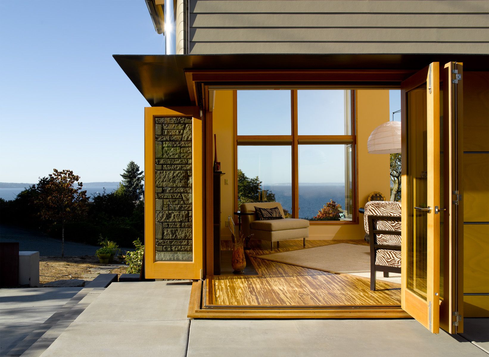 Slide-fold doors connect the living room to an outdoor terrace.