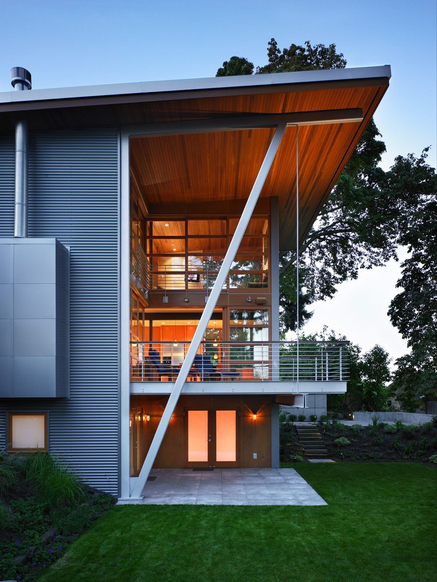 Indoor-outdoor livng on the two story covered deck.  A three story steel bracket both supports the roof above and the suspended deck below.