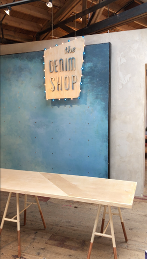 Denim  shop sign, wood table, and legs