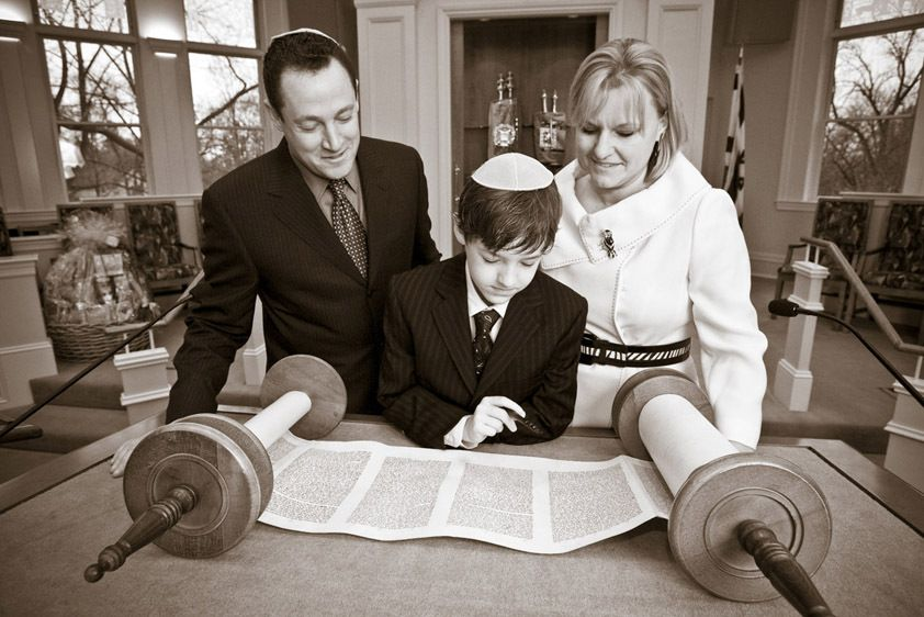 Ethan and his parents reading the Torah