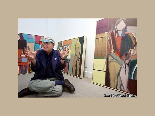 GEORGE LLOYD  , shown squatting on the floor  with  his paintings from early 70s  , at the  HACKETT FREEDMAN  Gallery , SanFrancisco CA  ,   on occasion of his solo exhibition in August 2000.