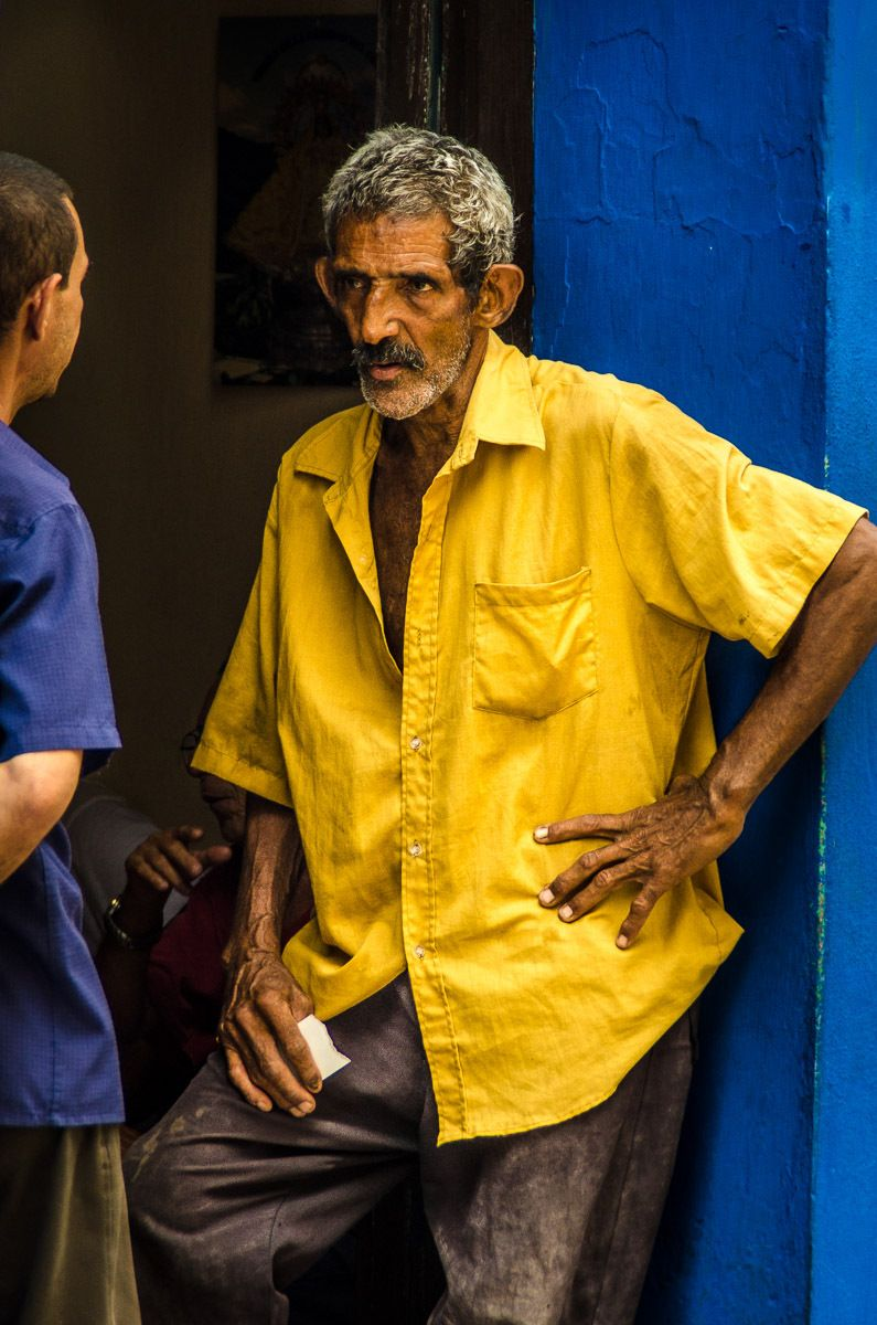 Cuban men in conversation along street in Santiago de Cuba.