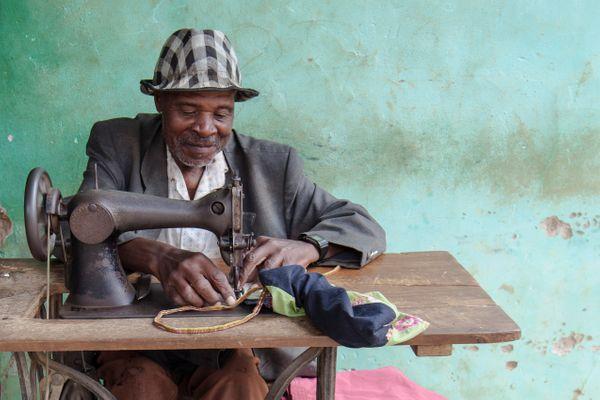 rwanda_man_sewing_street.jpg