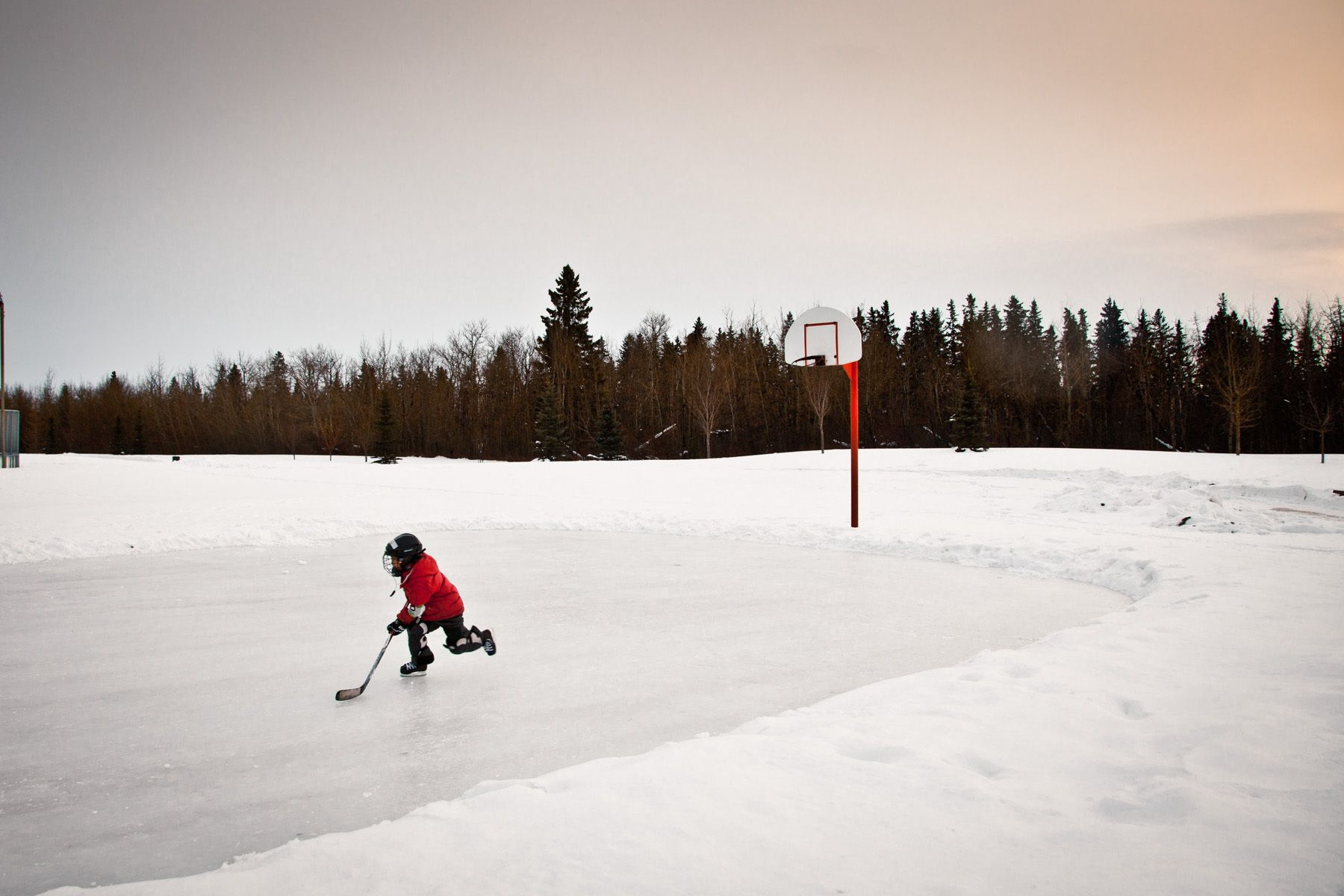 'Tis the Season?  A young hockey player practices his skating on a frozen basketball court in Alberta