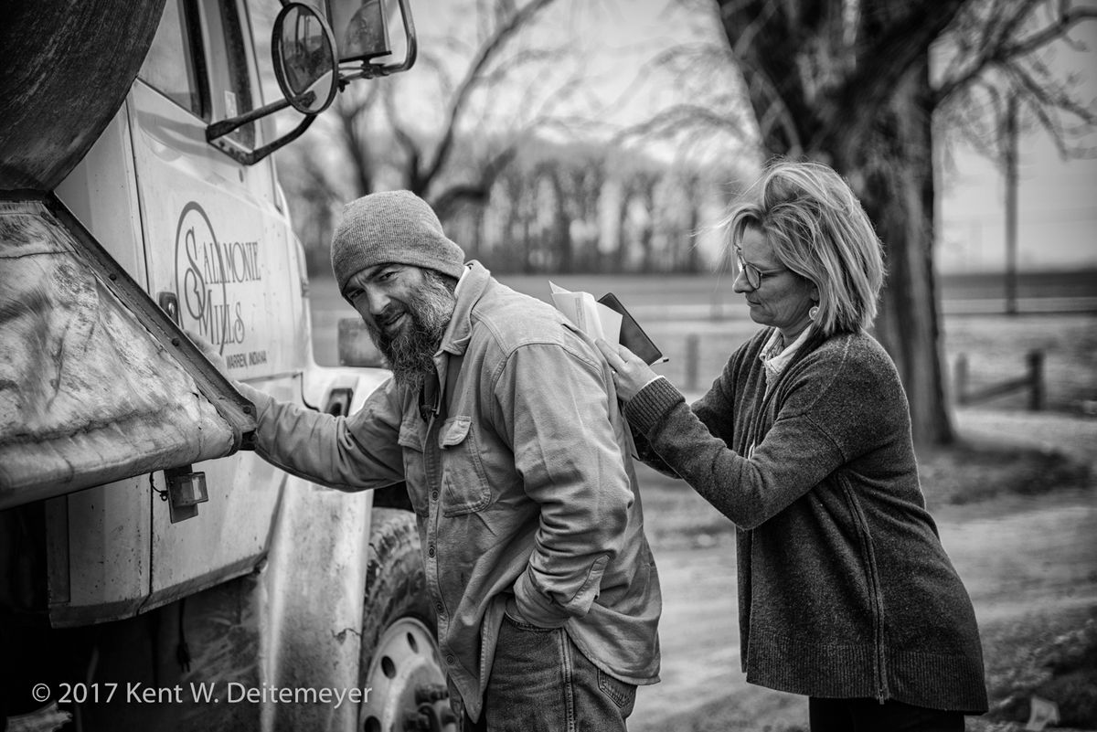 After receiving a delivering of cattle feed from Ernie, Kristen Wood uses his back to write him a check.