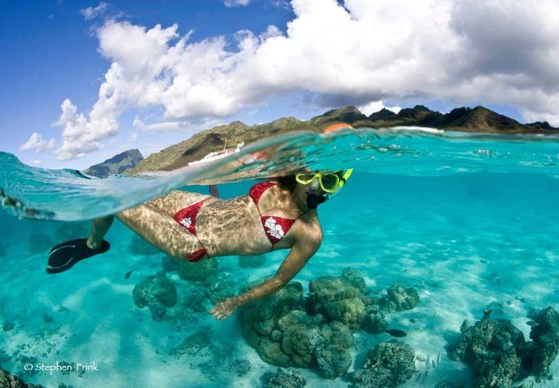 Over/Under of Female Snorkeler, Tahiti