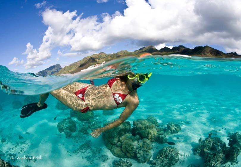 Over/Under of Female Snorkeler, Tahiti