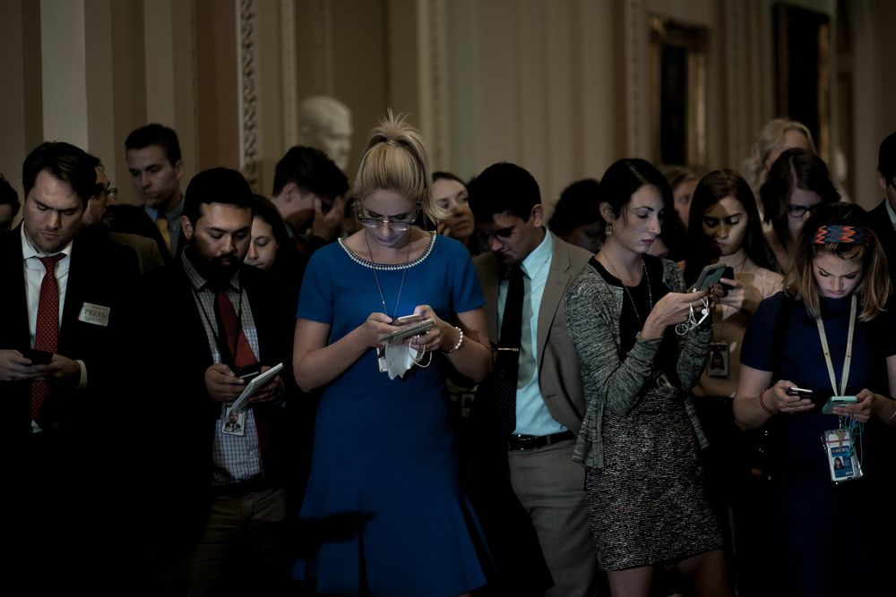 Reporters check their cell phones
