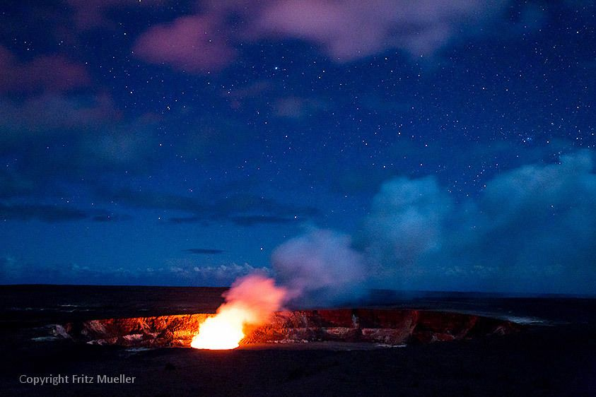 Clouds reflect glow from giant pool of molten lava in Halema`uma`u Crater in Hawaii Volcanoes National Park, Big Island of Hawaii