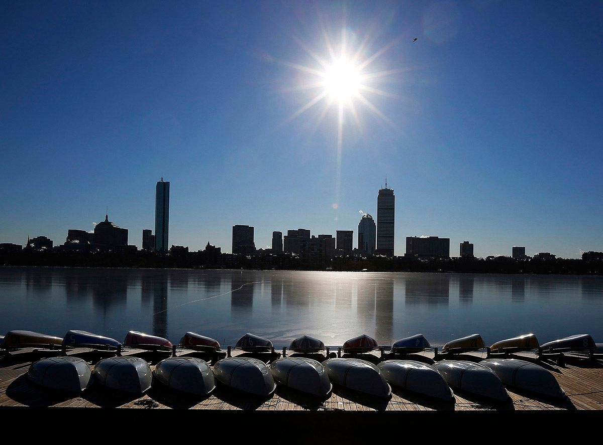 Sail boats sit on dock at the MIT Sailing Pavilion on the Charles River in front of the Boston skyline on cold winter day in Cambridge
