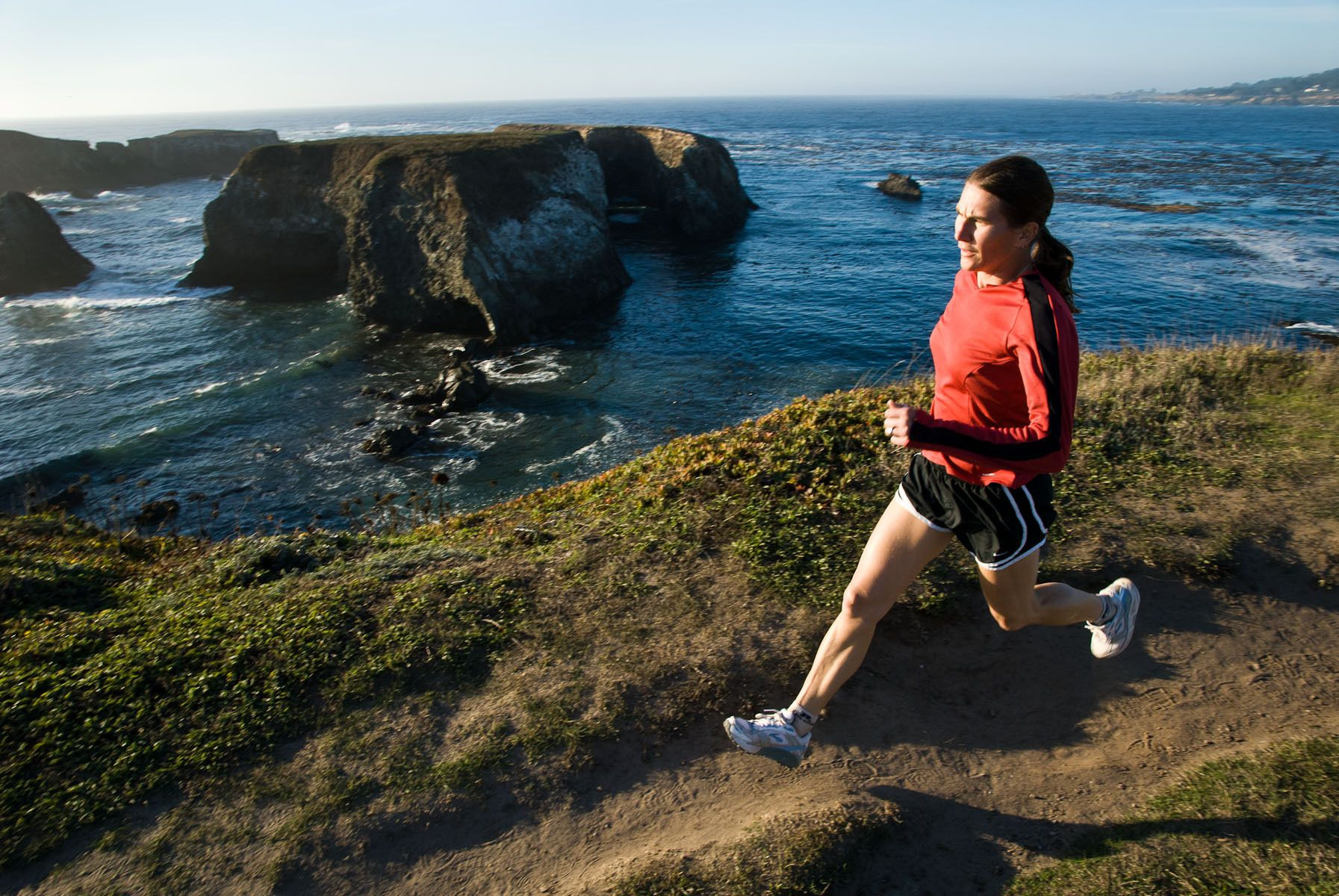 Woman Running on Coastal Trail
