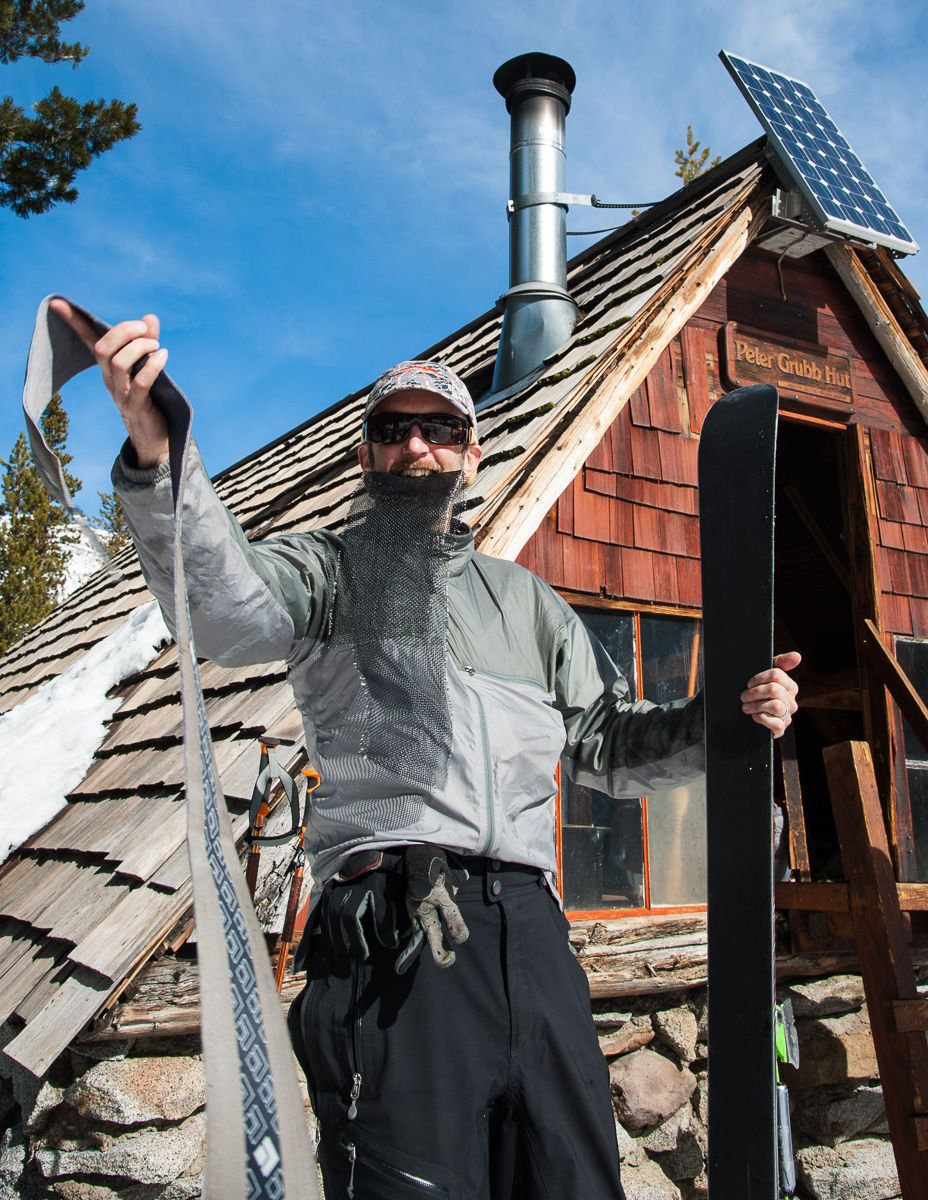 Skier Putting Climbing Skins on Skis in front of Peter Grubb Ski Hut