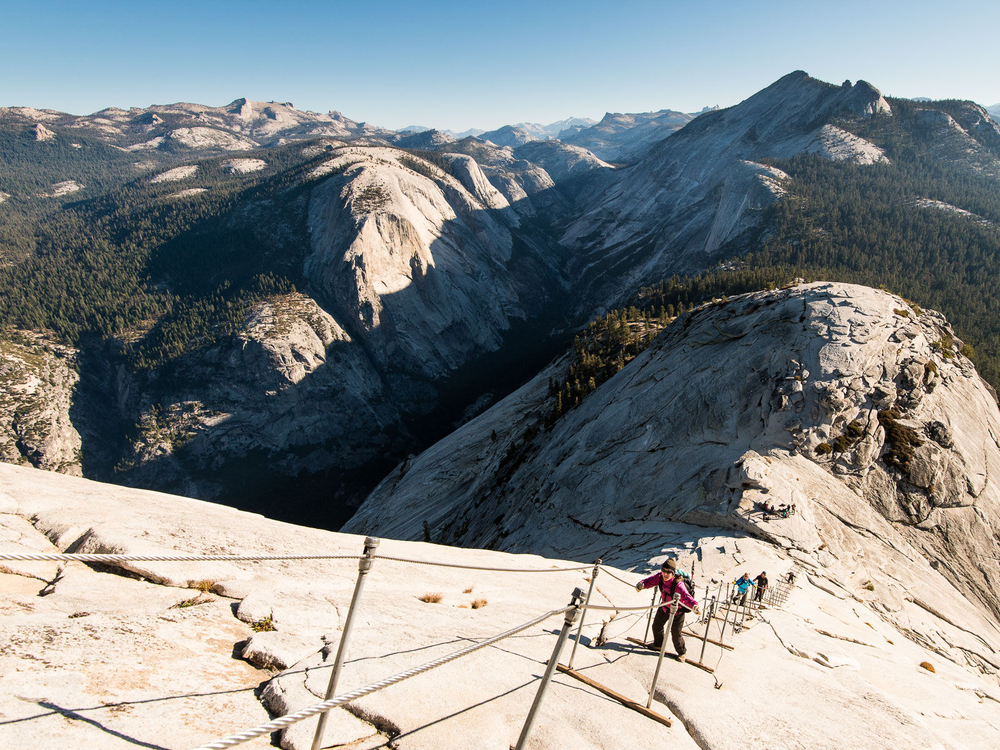 Woman climbs the Half Dome Cables