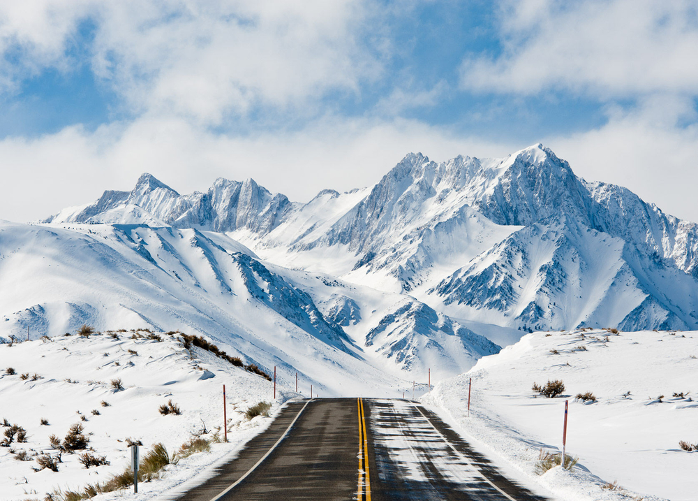 Road Leading Toward Snow Covered Mountains