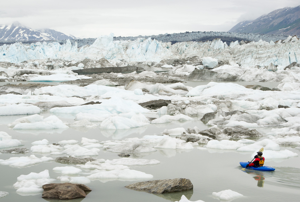 Kayaker Navigating Icebergs in Lowell Lake