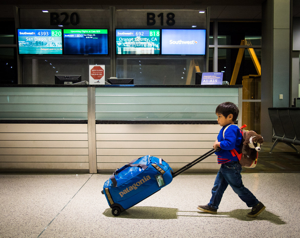 Young Boy and stuffed animal pushing luggage through the airport