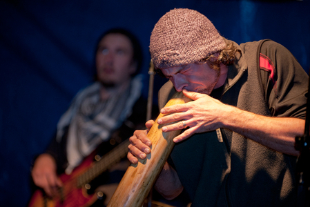 musician playing digereedoo at local outdoor concert