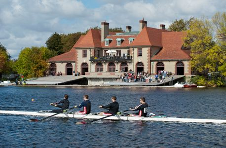 Head of the Charles rowing crew passing Harvard Boat  House