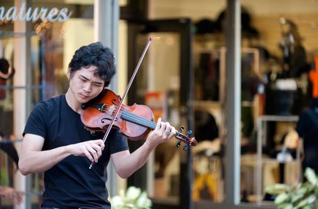 Street musician playing violin at promenade