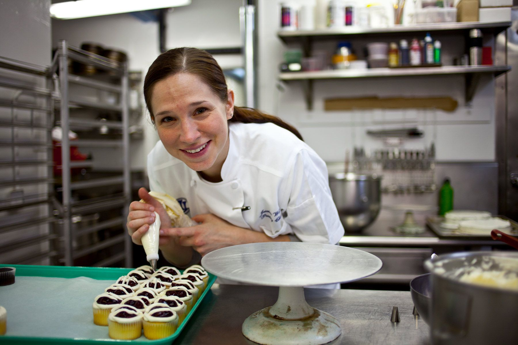 Jessica Weiss in the Union League of  Chicago kitchen icing cupcakes.  Jessica is  Executive Pastry Chef at Marta of the Union Square Hospitality Group, has also been Executive Pastry Chef of Maialino of the Union Square Hospitality Group.