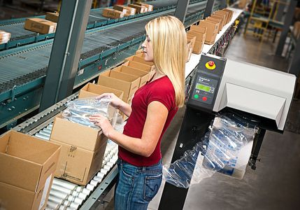 Carton packer uses Sealed Air packing on distribution center packing line