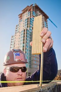 Construction worker checks level at residential tower construction site