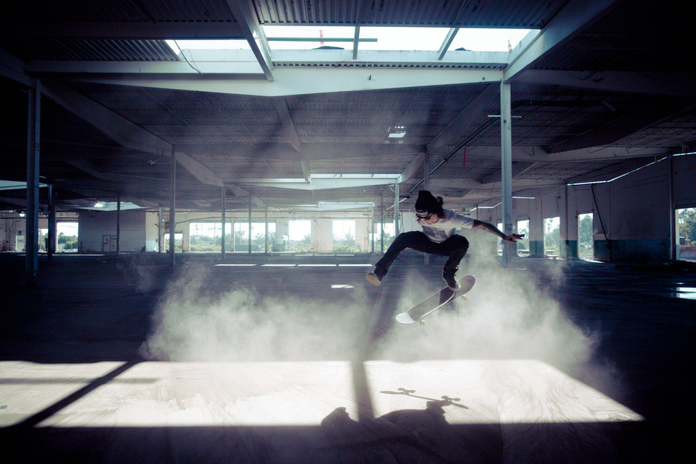 Skateboarder ollies in dusty warehouse