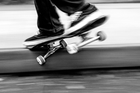 Skateboarder grinds curb going fast