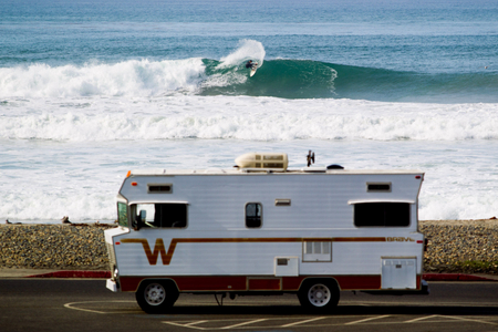 Surfer turns on a wave in front of Winnebago RV
