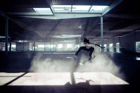Skateboarder ollies in dusty warehouse