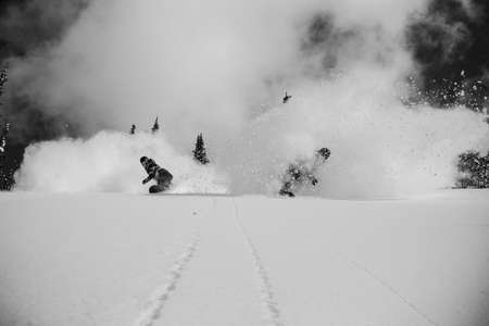Snowboarders slash powder side by side
