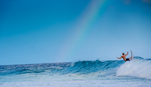 Surfer turns on a wave under a rainbow