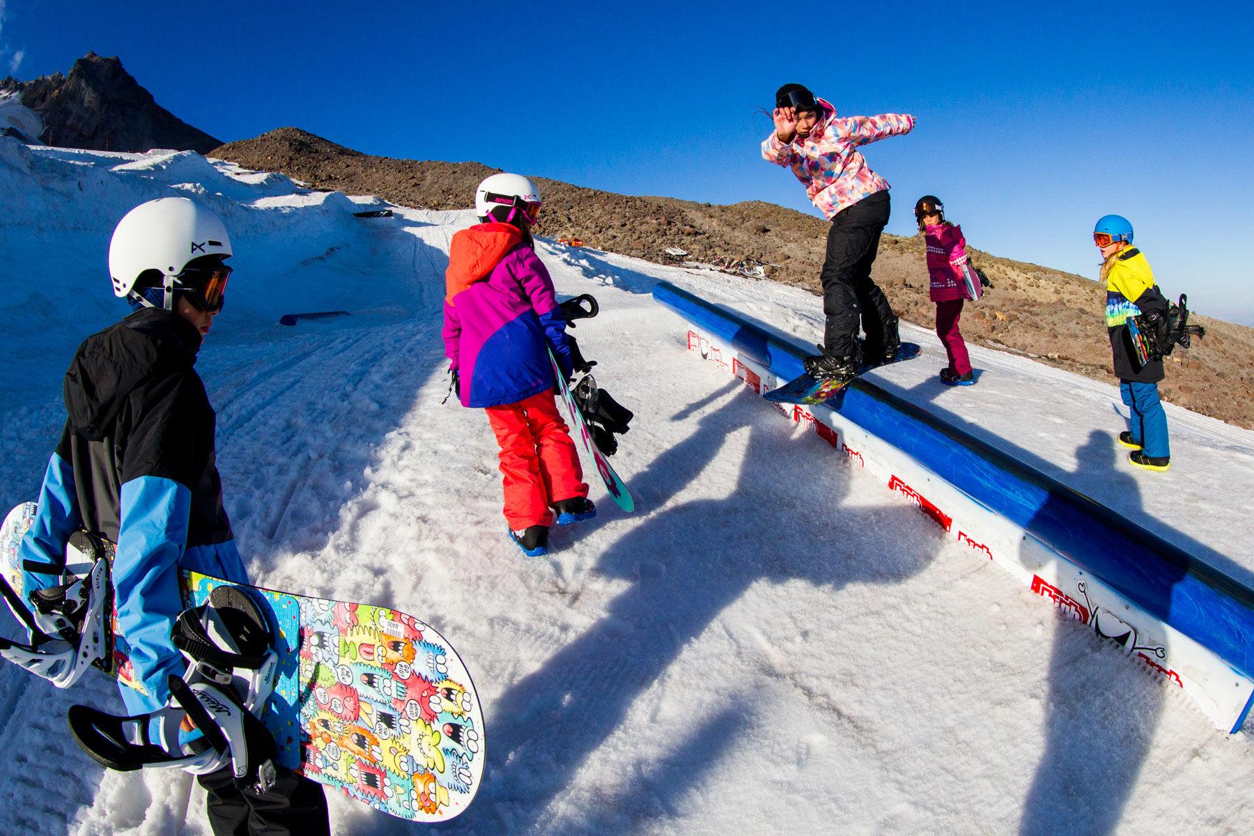 Kid slides down rail on snowboard