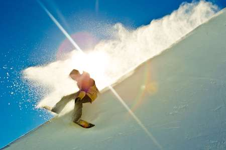 Snowboarder slides down halfpipe through the sun