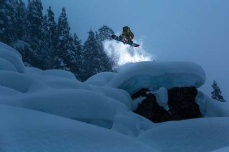 A snowboarder flies above a field of backcountry powder pillows